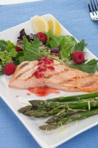 Grilled salmon with raspberry dressing served with asparagus and green salad, healthy meal.