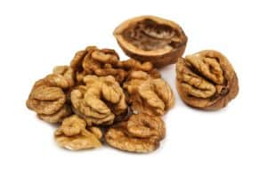 heap of delicious peeled walnuts on white background